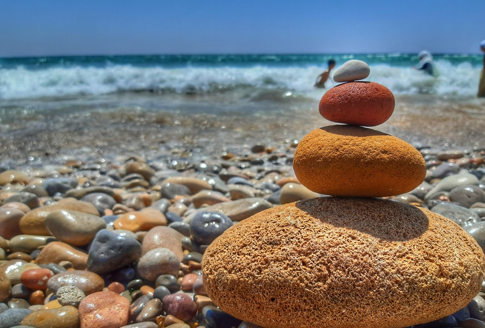 stack of orange stones on a beach