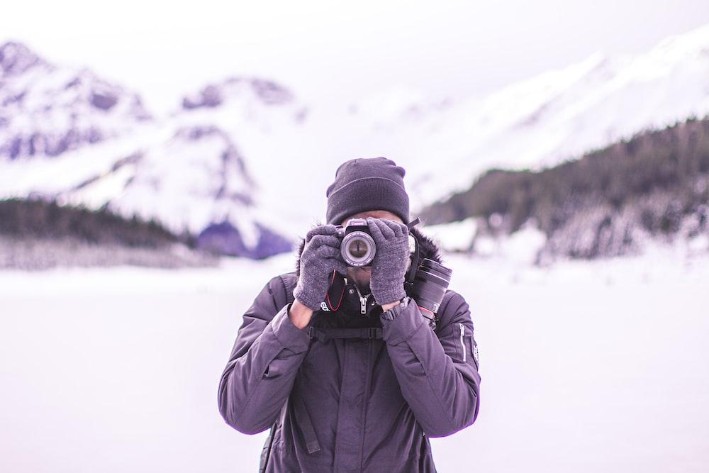man in black coat holding DSLR camera
