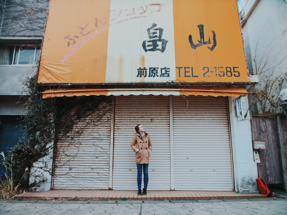 woman wearing beige trench coat standing behind of gray shutter door