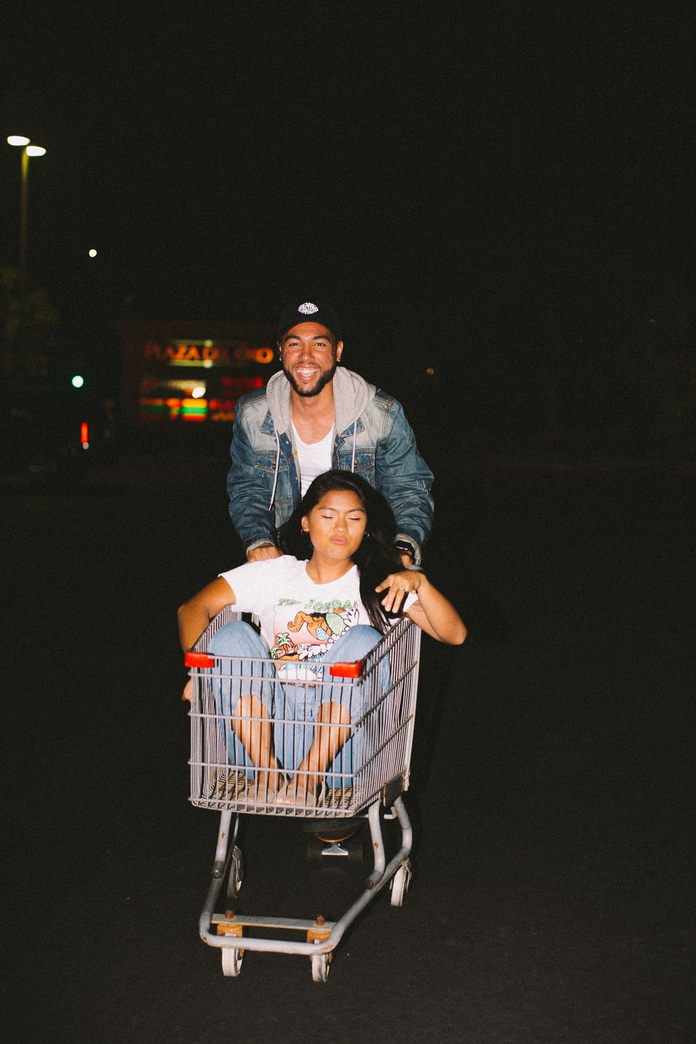 woman in shopping cart pulled by a man