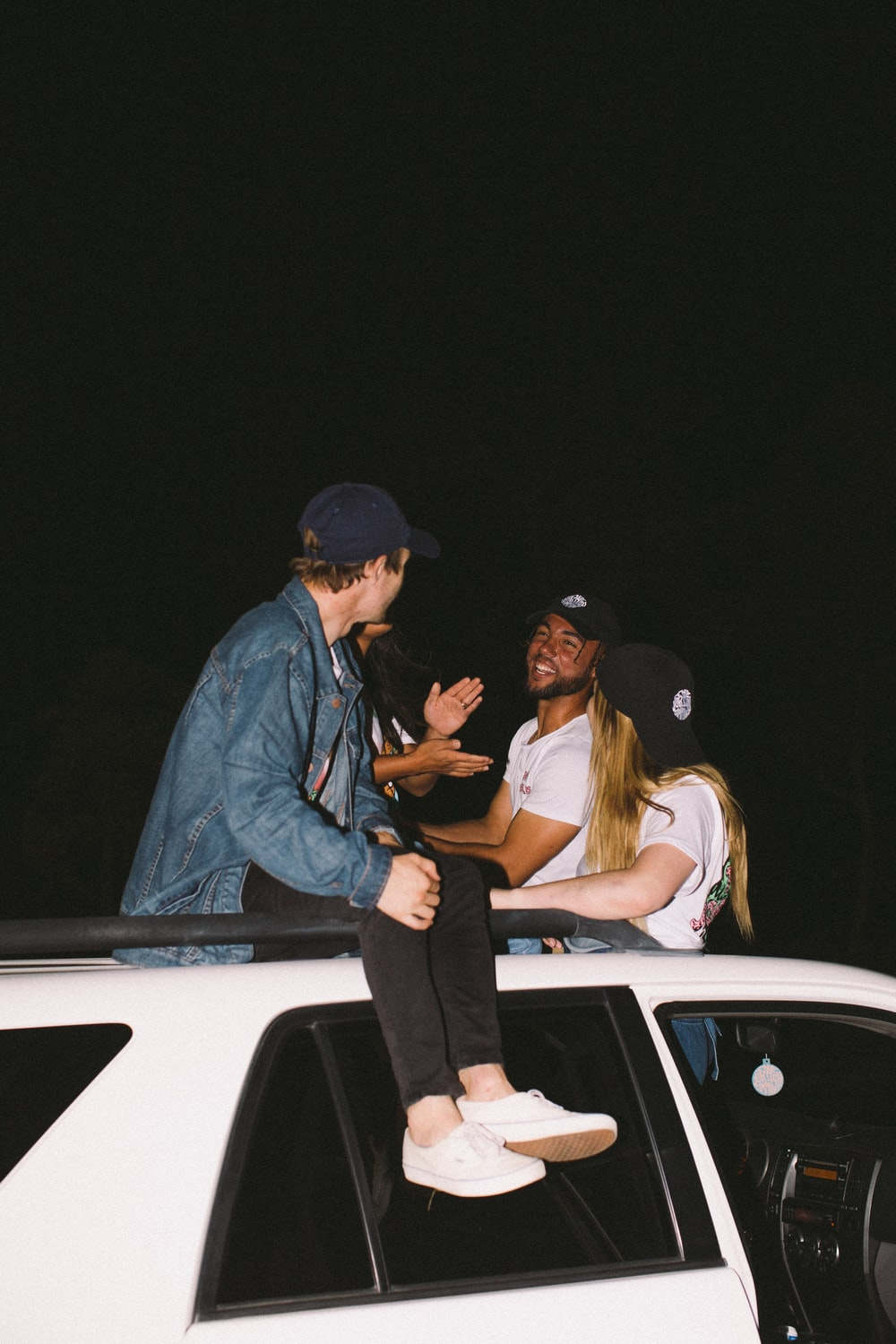 three person sitting on vehicle roof