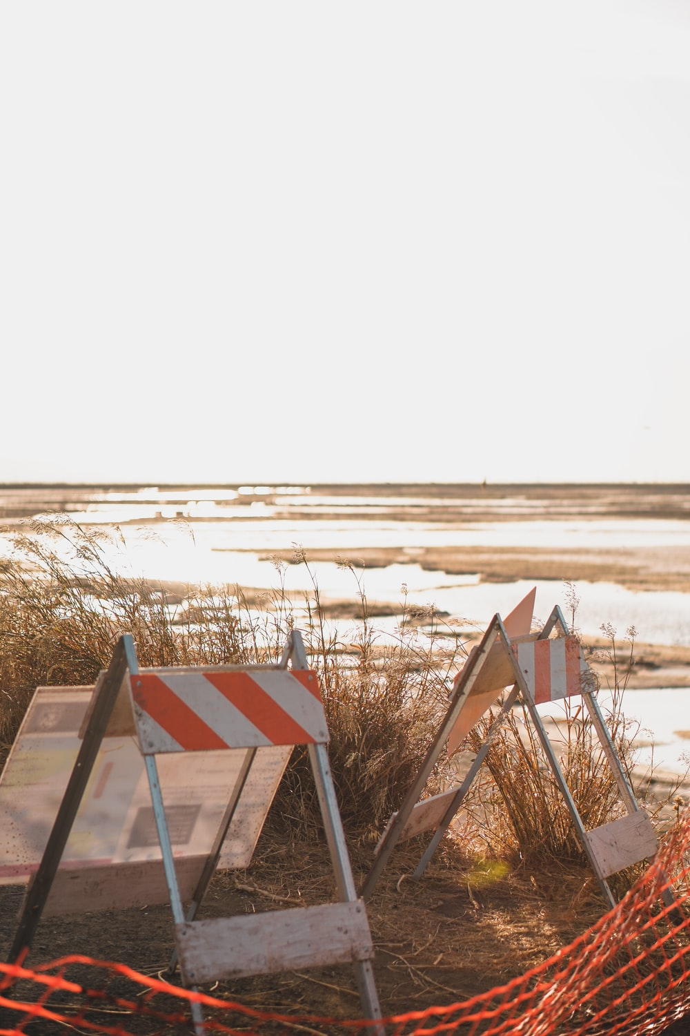 two folding signs on soil ground near body of water