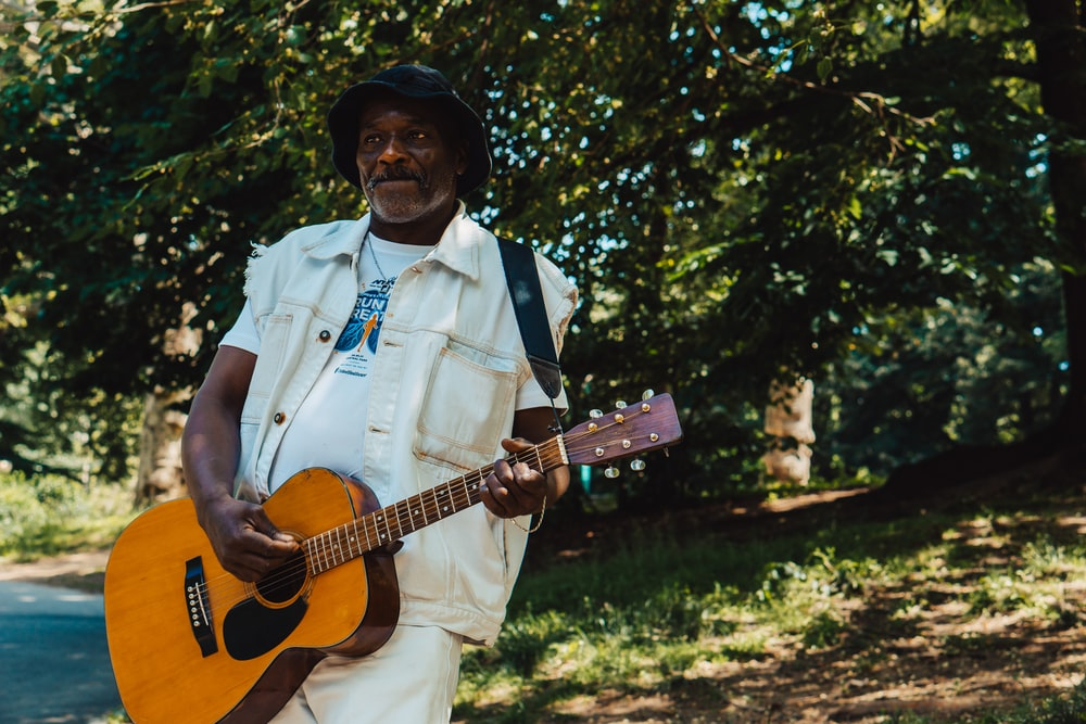 man standing and playing guitar during daytime