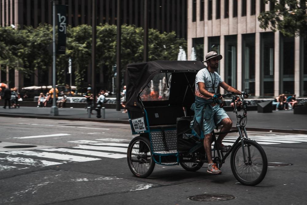 man driving pedal rickshaw on road