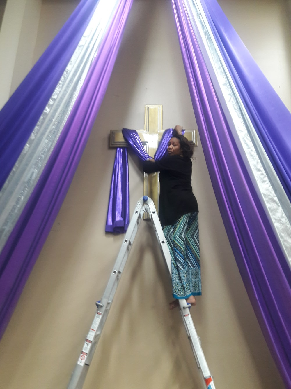 woman on a-frame ladder holding blue textile on wall cross
