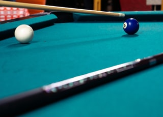 cue ball and 2 ball on pool table near cue sticks