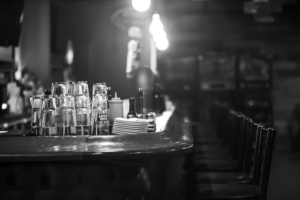 grayscale photo of drinking glass on tables