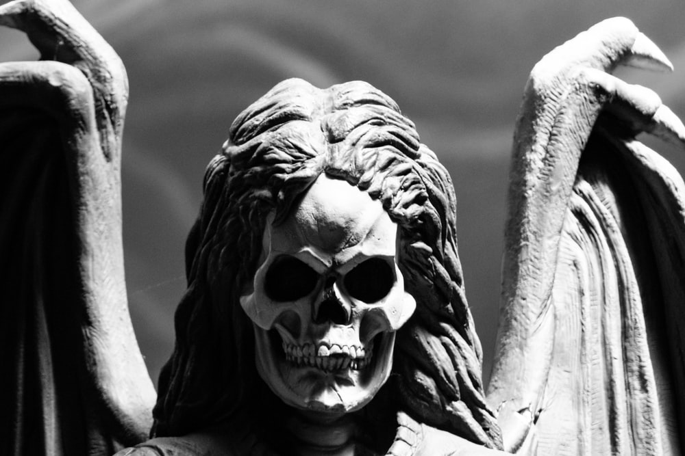 skull-faced human with wings statue