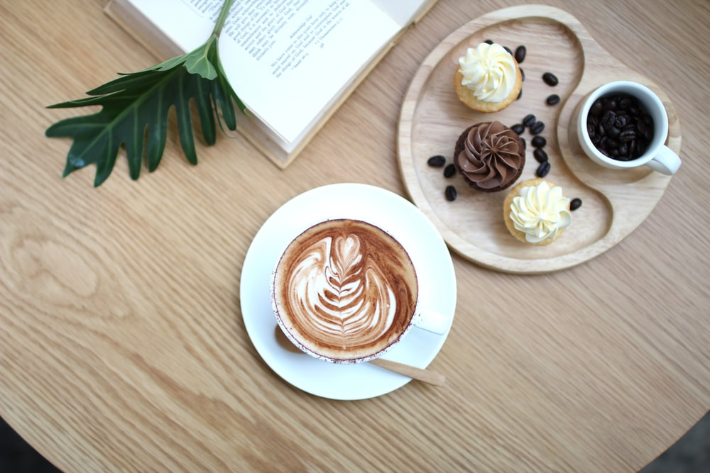 flat lay photography of cup and cupcakes