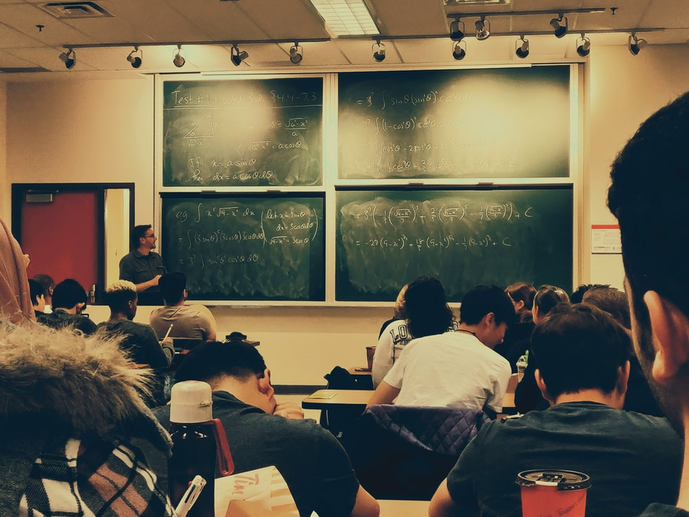 student sitting on chairs in front of chalkboard