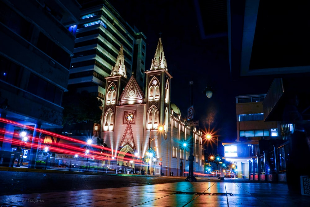 city with high-rise buildings showing church during night time