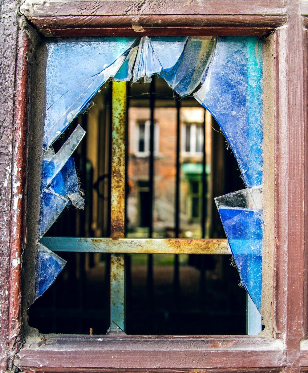 closed brown wooden framed broken window