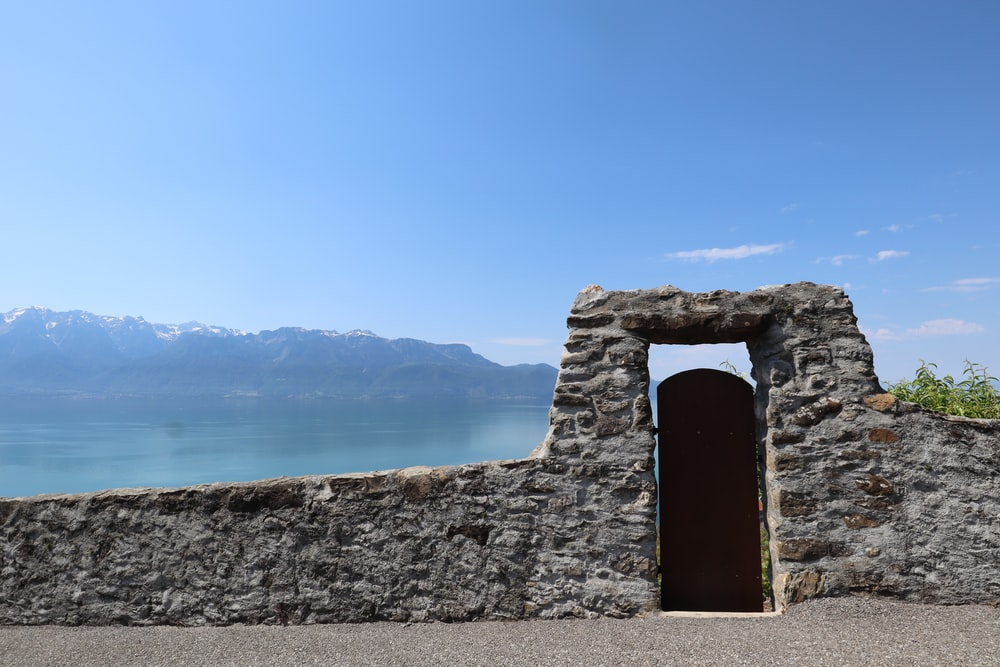 gray stone gate viewing calm sea and mountain under blue and white skies