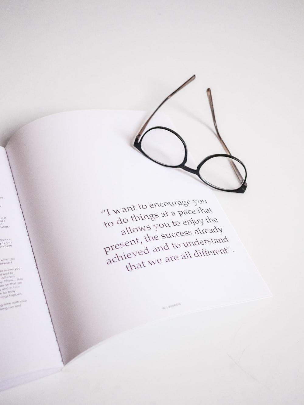 black-framed eyeglasses on opened book