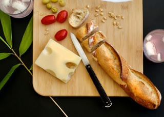 sliced bread near cheese, three red tomatoes, and nuts on wooden chopping board