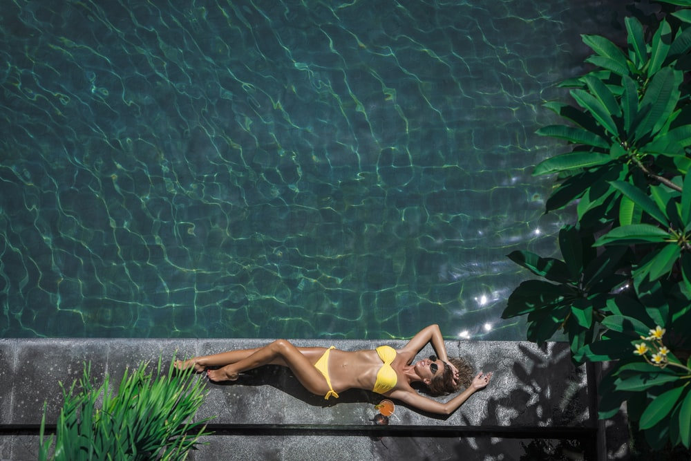 woman lying beside body of water