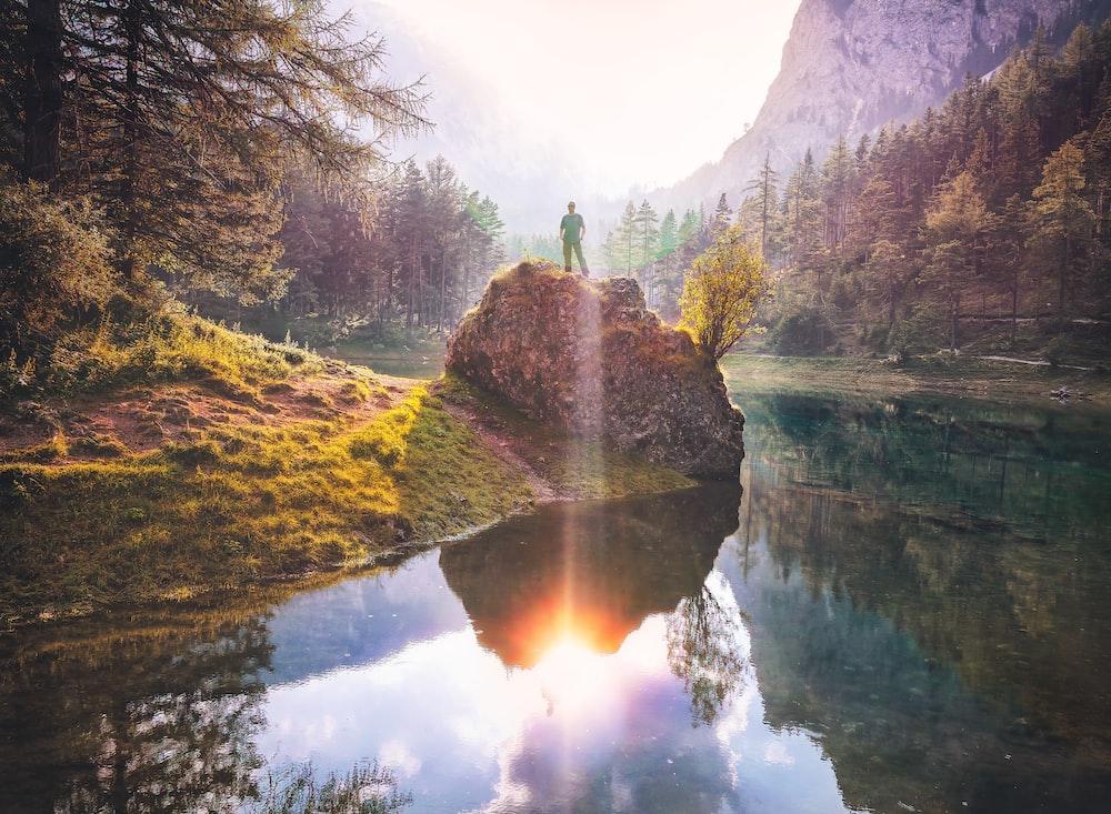 man standing on rock beside lake