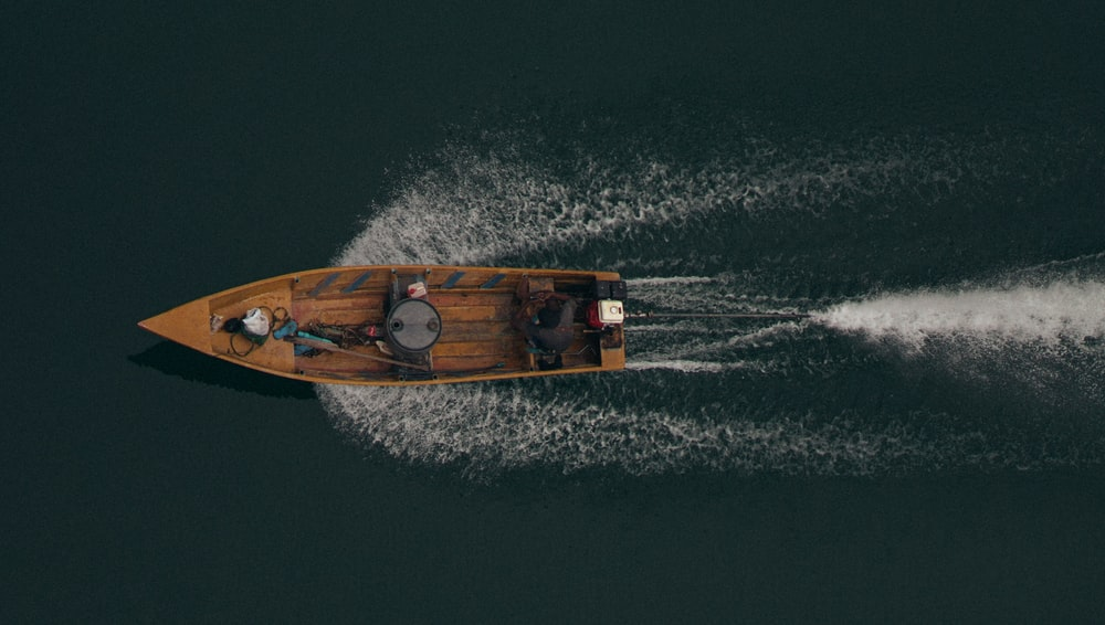 brown motor boat on body of water