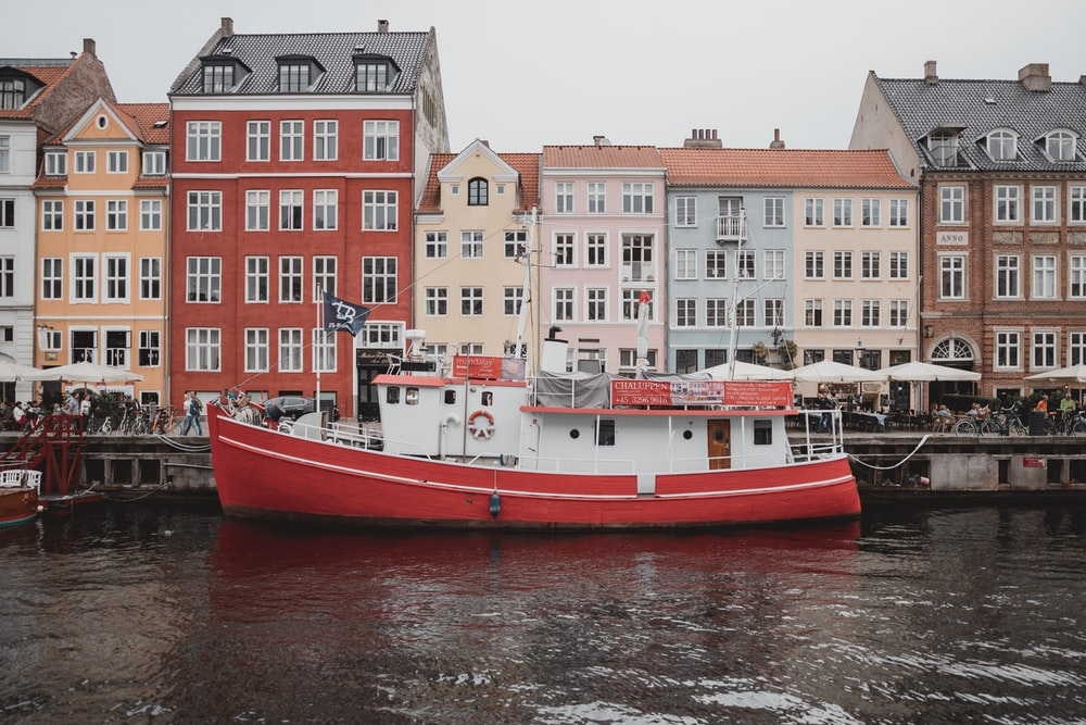 white and orange boat on water near buildings