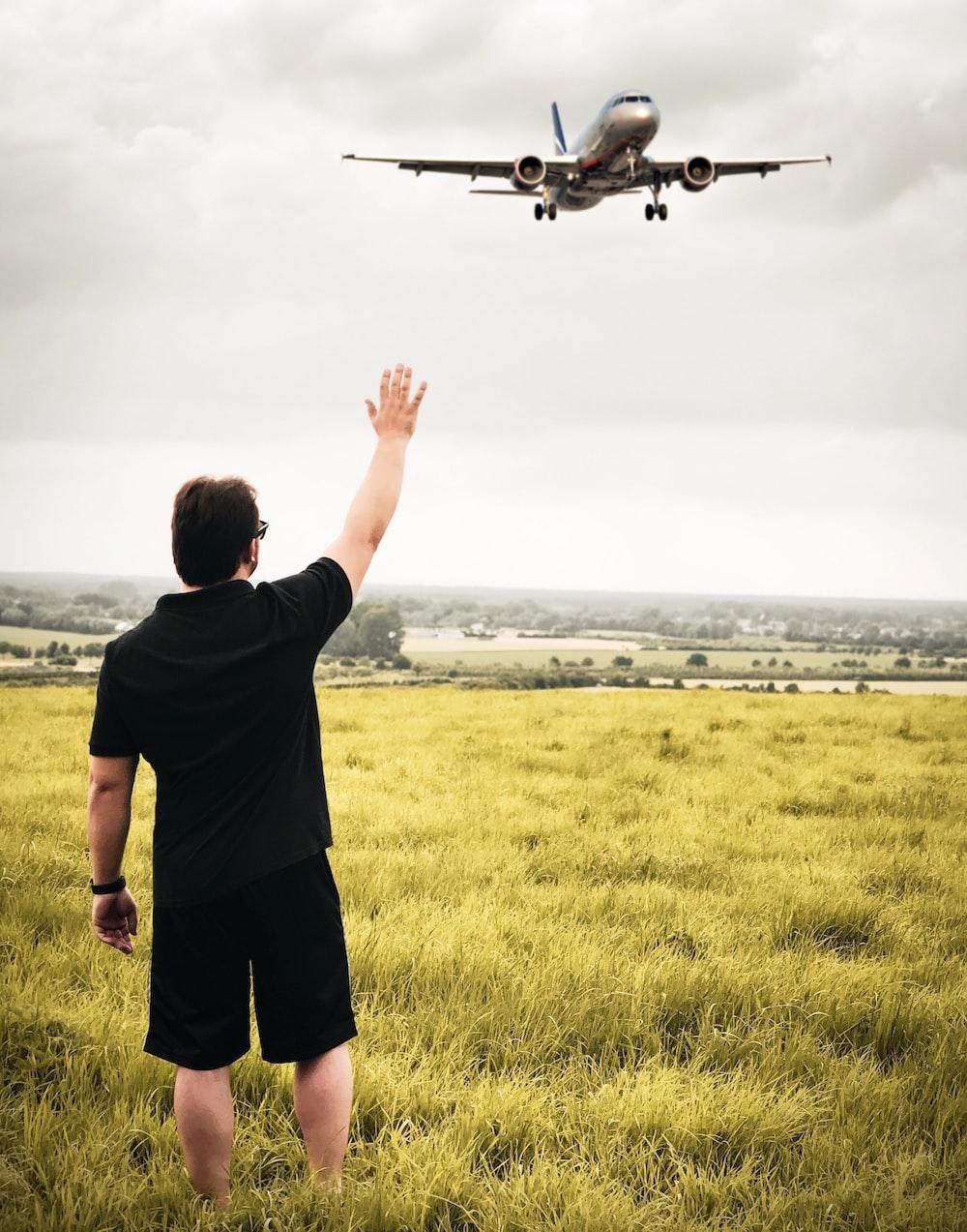 man raising his right hand looking at plane