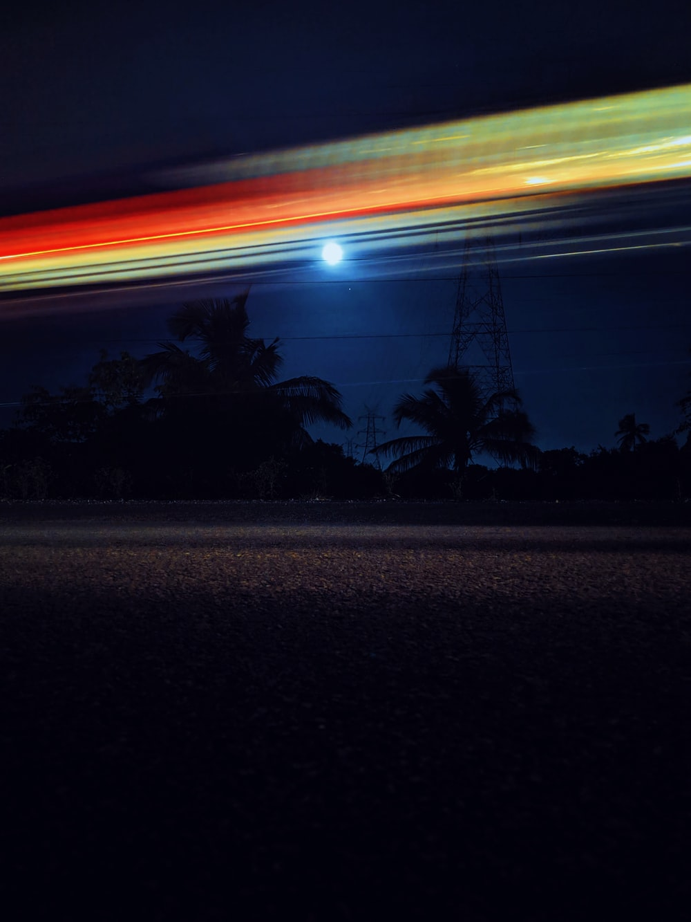 time-lapse photography of road beside trees and transmission tower