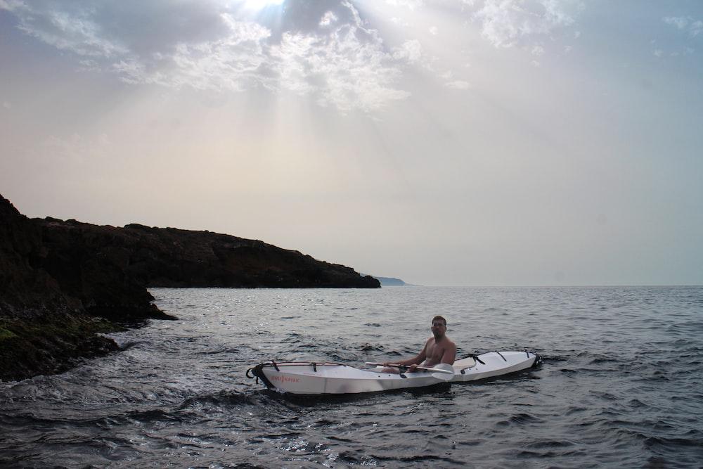 topless man sitting on white kayak near beach cliff