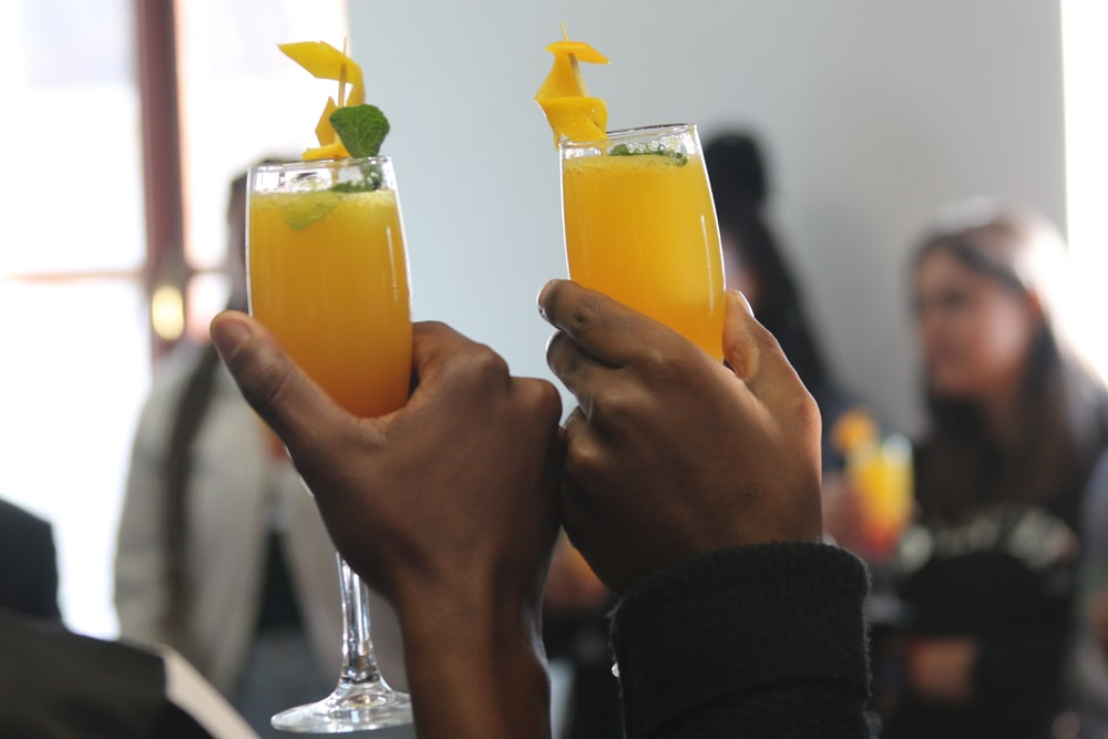 yellow beverage in footed glasses