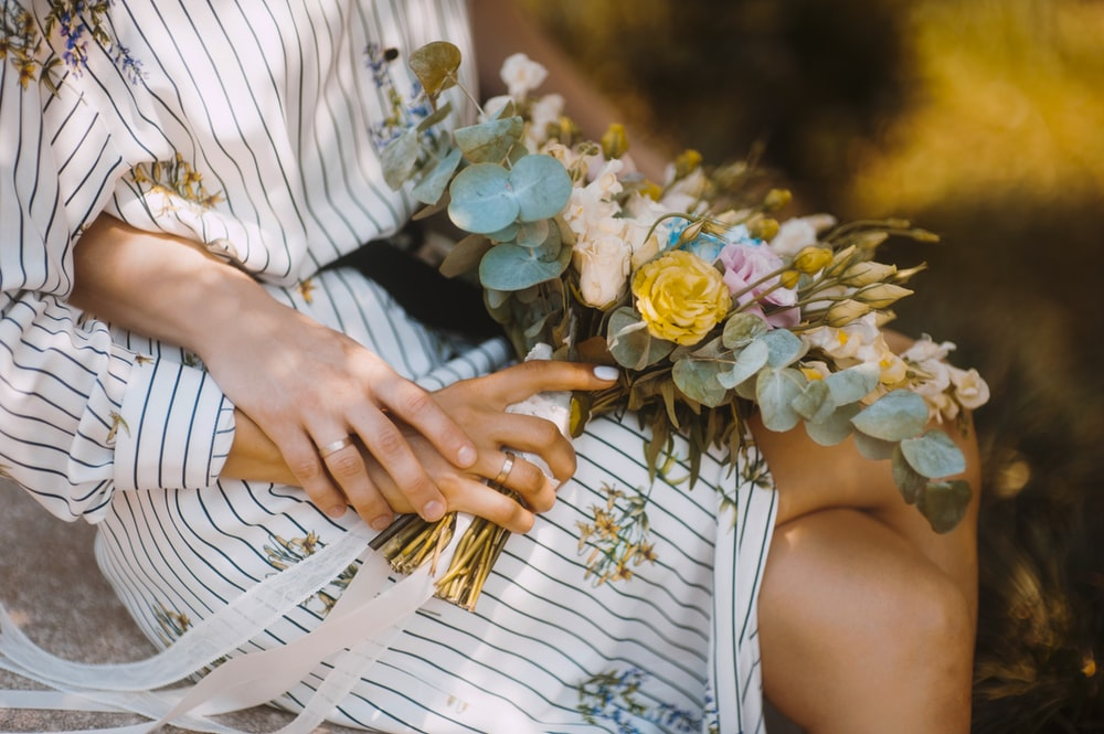 selective focus photography of sitting woman holding flower bouquet