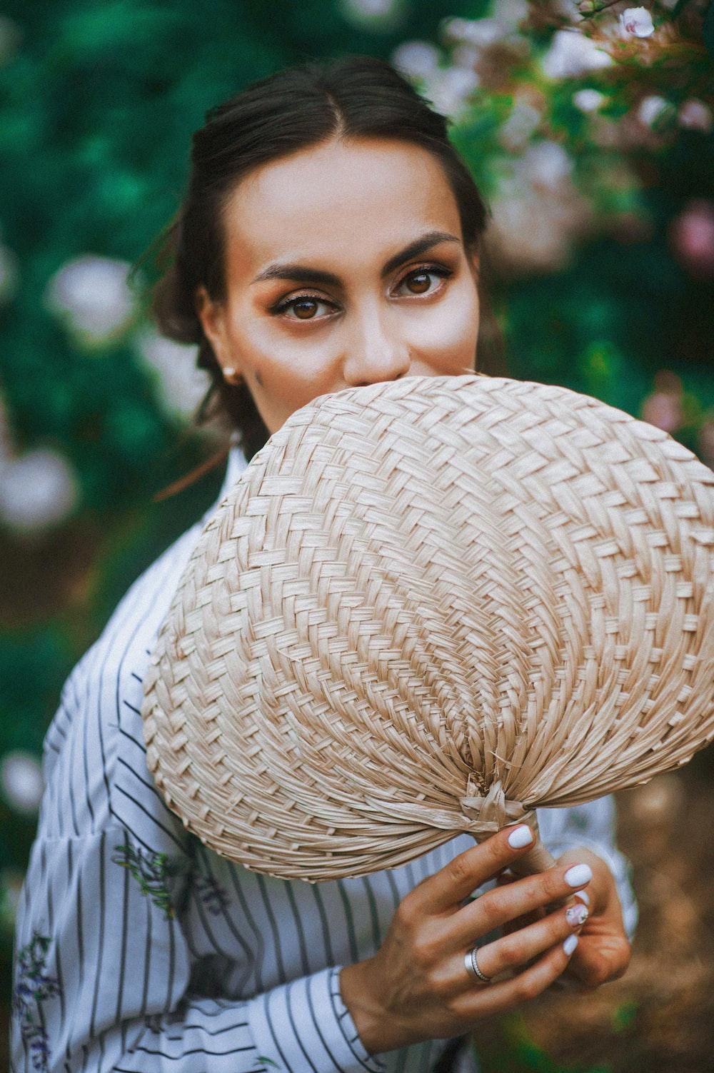 woman holding brown hand fan