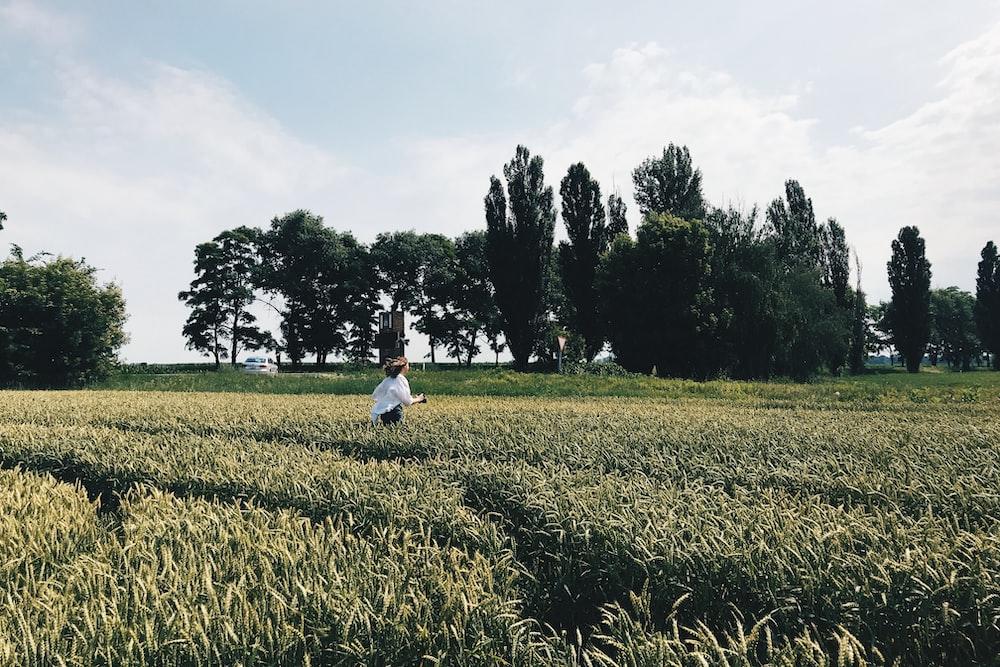 woman wearing white long-sleeved top walking during daytime