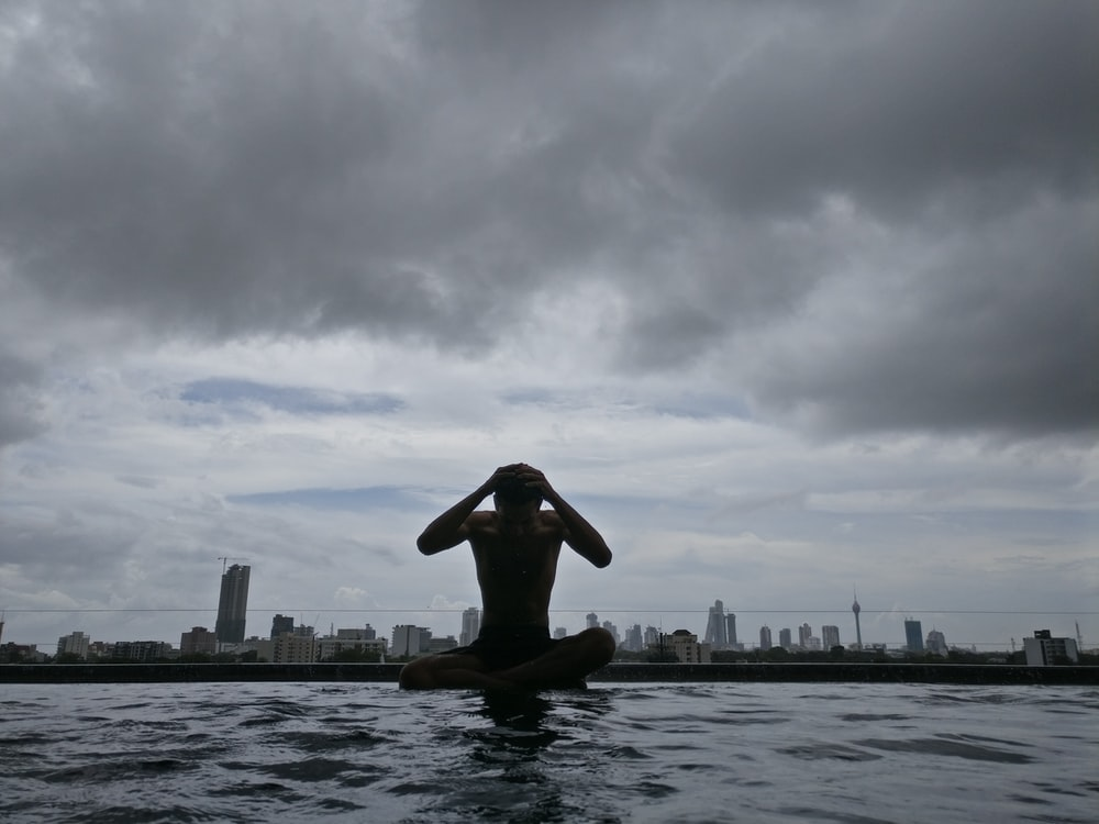 photography of man on body of water under cloudy sky during daytime