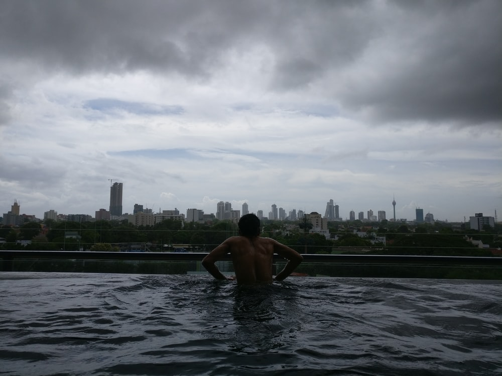 man on swim pool across city building during cloudy daytime