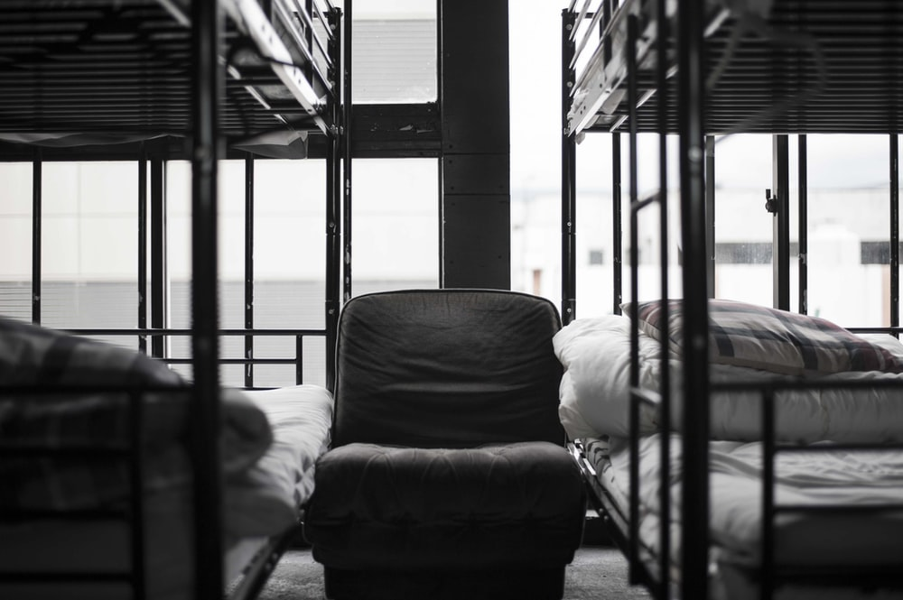 grayscale photo of bunk bed and chair