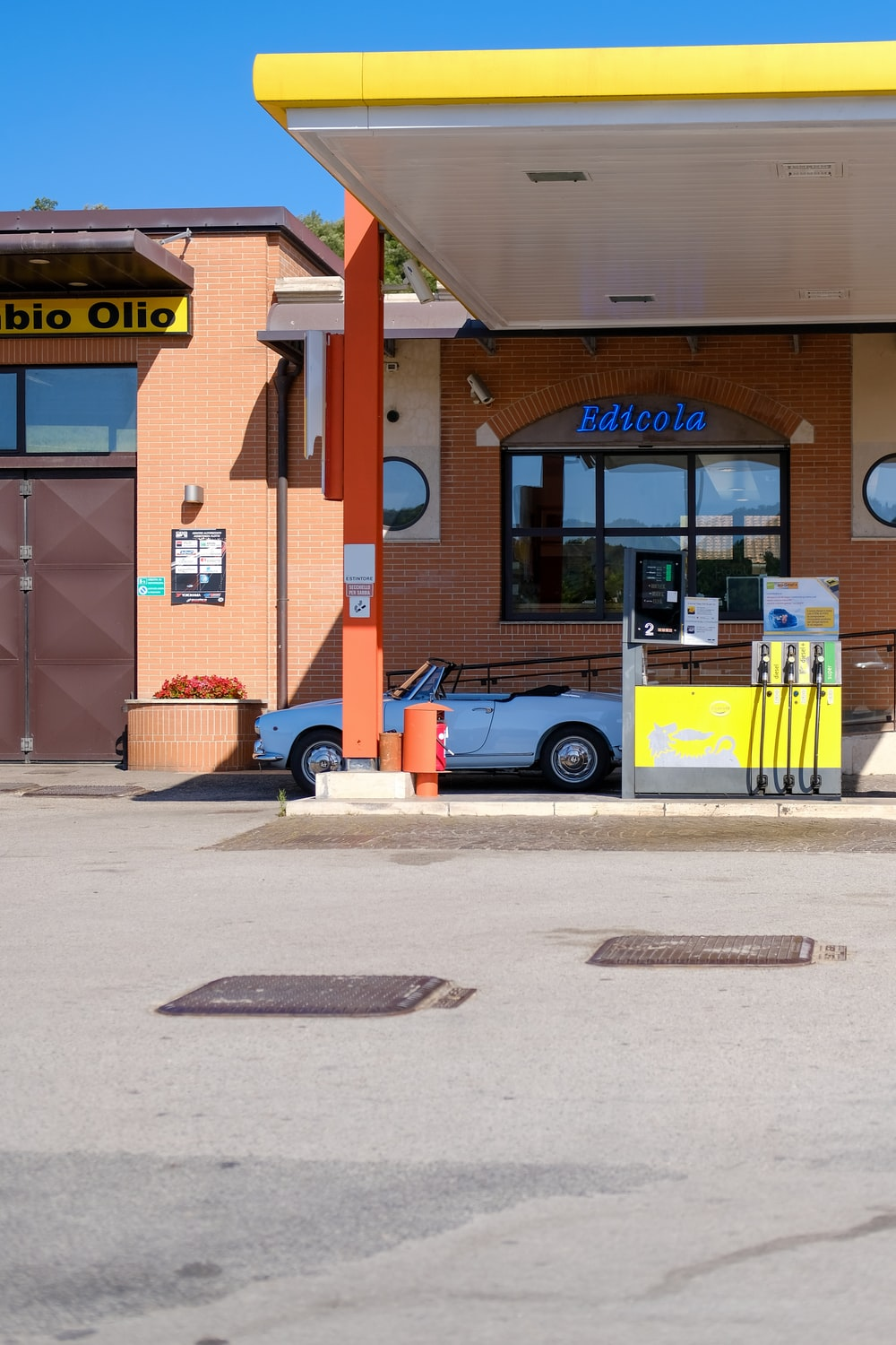 white convertible on gasoline station