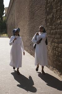 two nun walking near wall