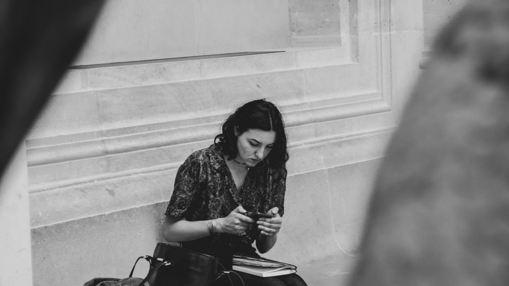 grayscale photography of woman using gadget