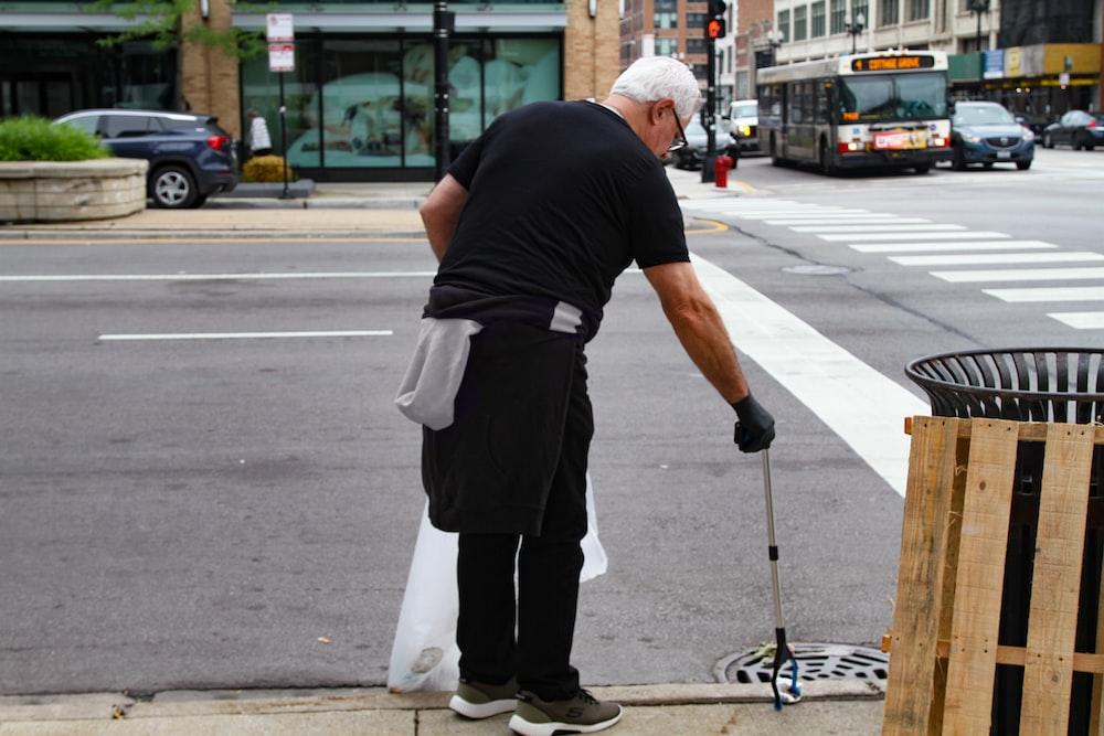 man in black T-shirt picking garbage on roadside during daytime