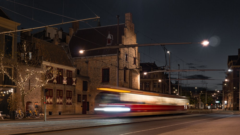 time-lapse photography of bus on road at nighttime