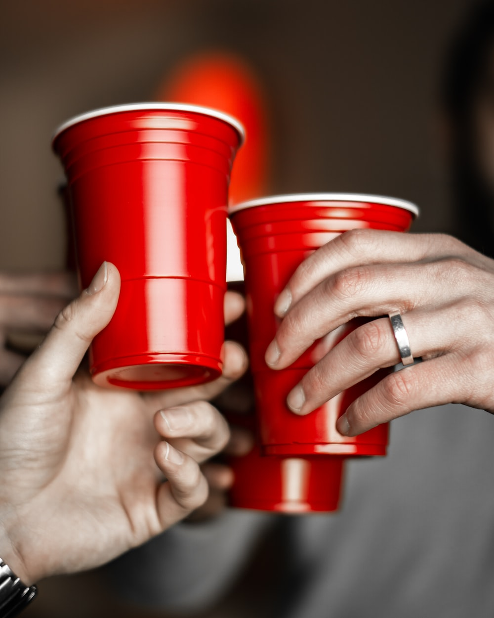 person holding red solo cups