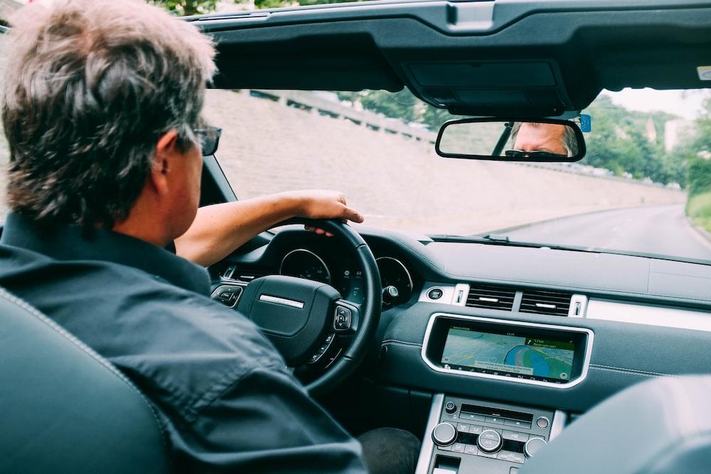 man driving vehicle during daytime