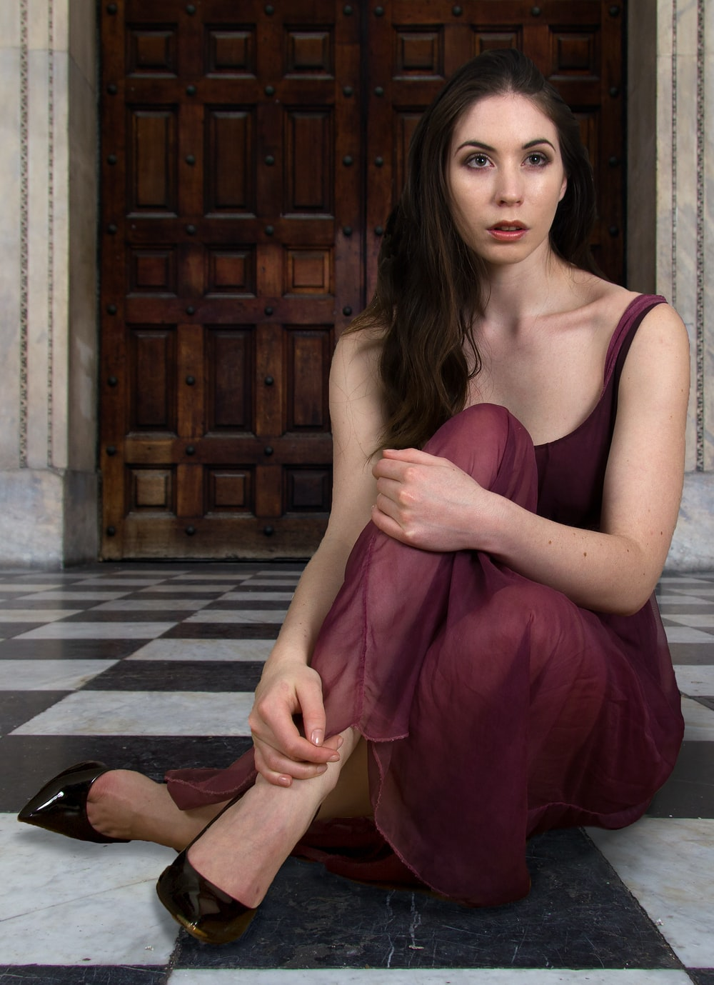 woman in burgundy dress sits on the floor