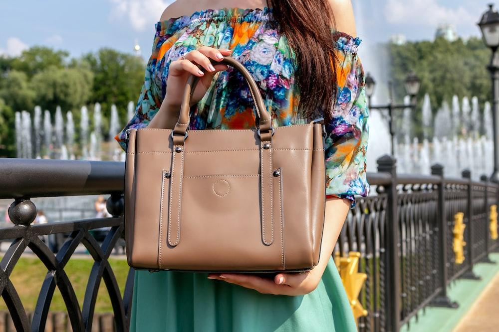 woman holding brown leather handbag