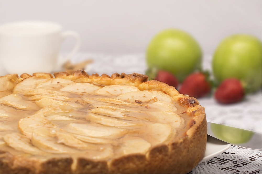 pie with cream on top near strawberry fruits