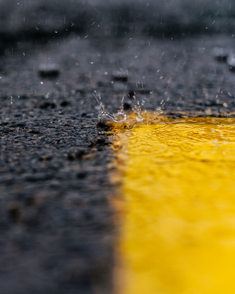 water droplets falling to yellow paint on gray surface