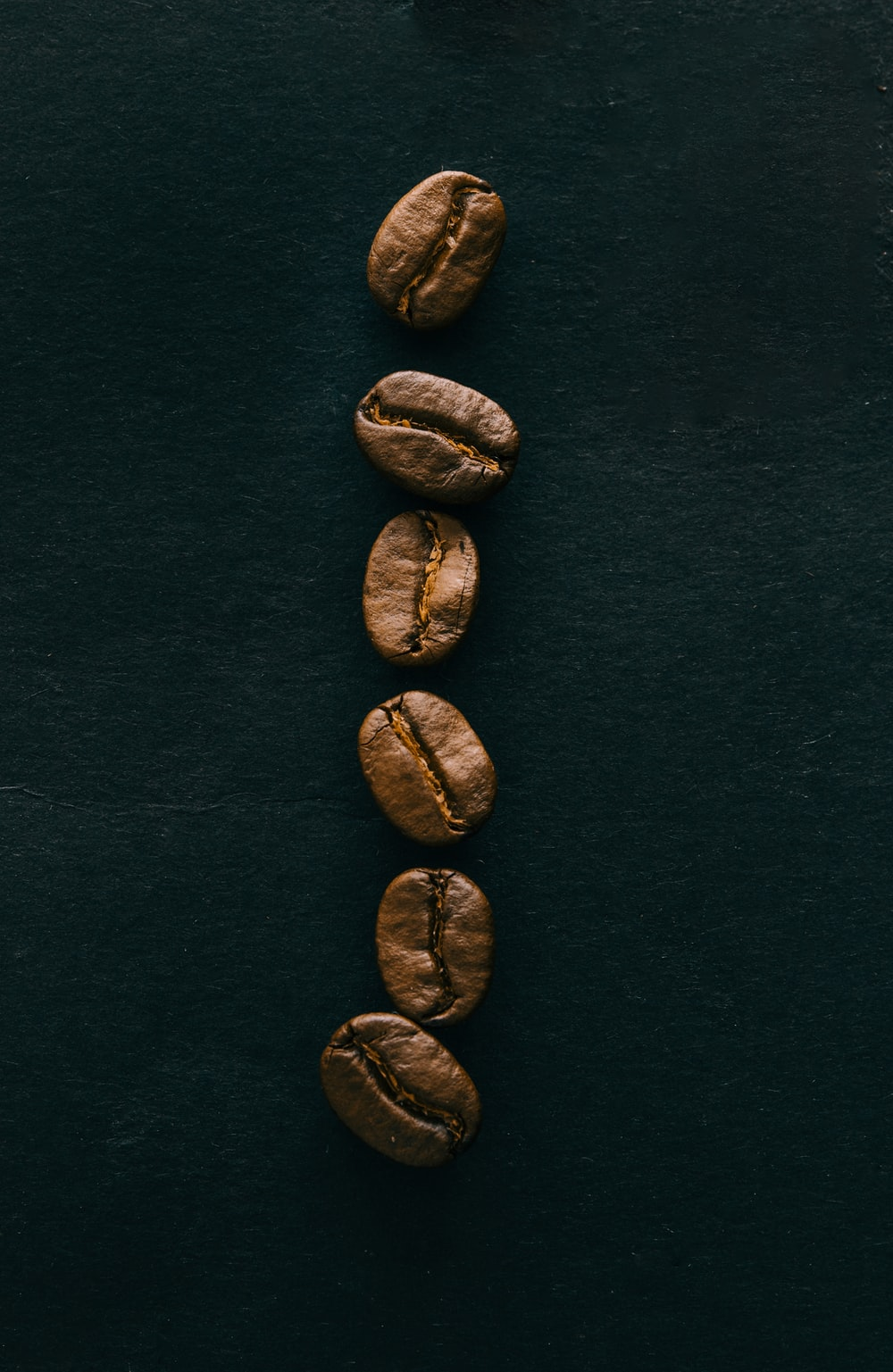 six brown coffee beans on blue surface