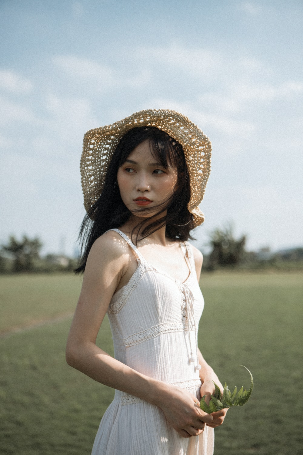 woman wears hat and white sleeveless dress at green grass