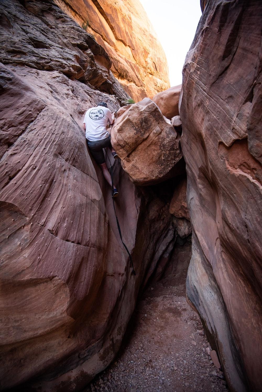 man climbing on brown rock formation during daytime
