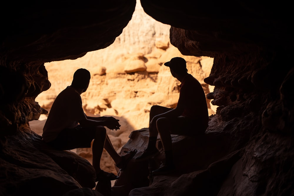 two person under a cave during daytime close-up photography