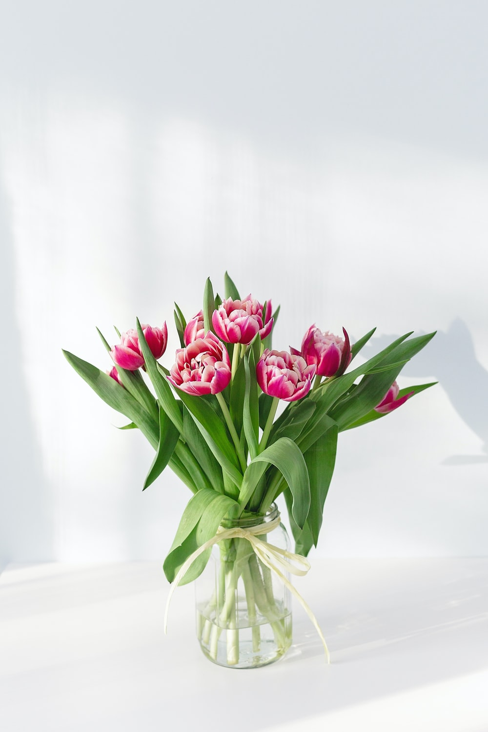 pink petaled flower centerpiece in clear glass vase