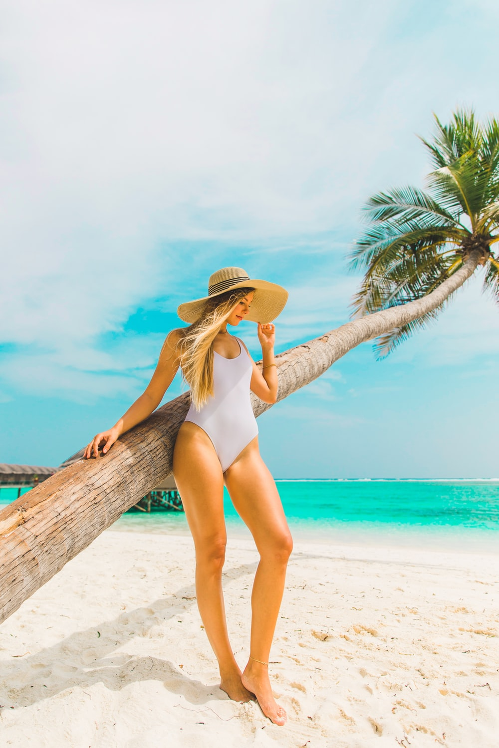 woman wearing white swimsuit leaning on tree during daytime